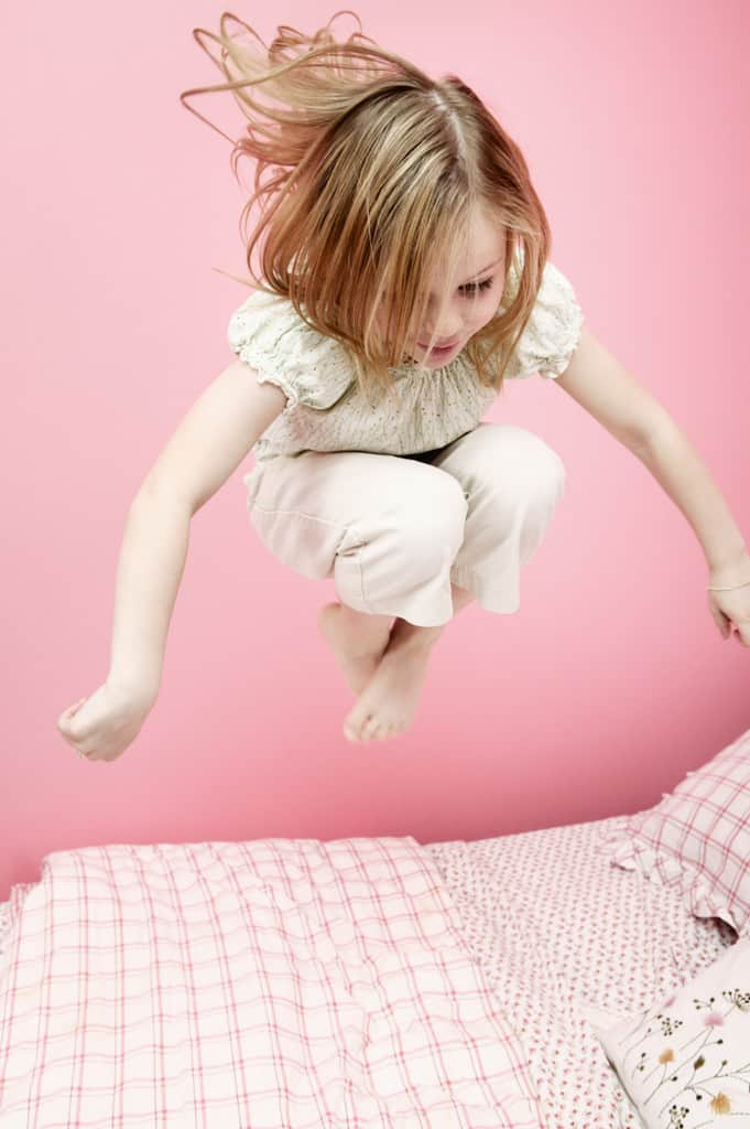 Girl Jumping on Bed --- Image by © Royalty-Free/Corbis